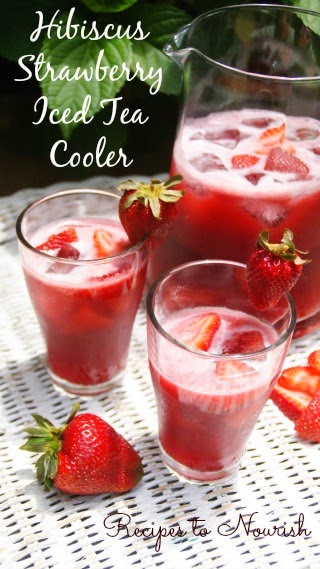 Hibiscus strawberry herbal iced tea in glasses and a pitcher with fresh strawberries.