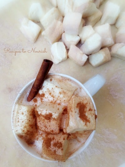 Homemade marshmallows in a mug of hot chocolate dusted with cinnamon.