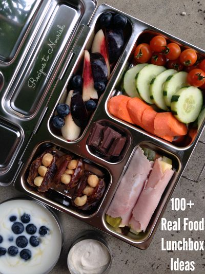 Stainless steel lunchbox full of fresh veggies, fresh fruit, macadamia stuffed dates, yogurt with blueberries, ham wrapped pickles and 3 squares of chocolate.