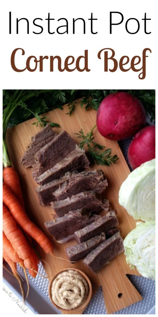 Slices of corned beef on a cutting board with carrots, cabbage and red potatoes.