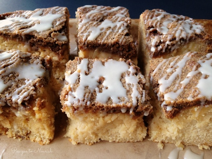 Large squares of coffee cake with streusel topping and a glaze drizzle on the top.