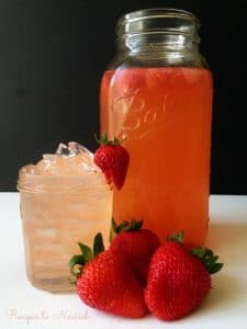 Strawberry switchel in a half gallon mason jar and over ice in a mall jar with fresh strawberries.