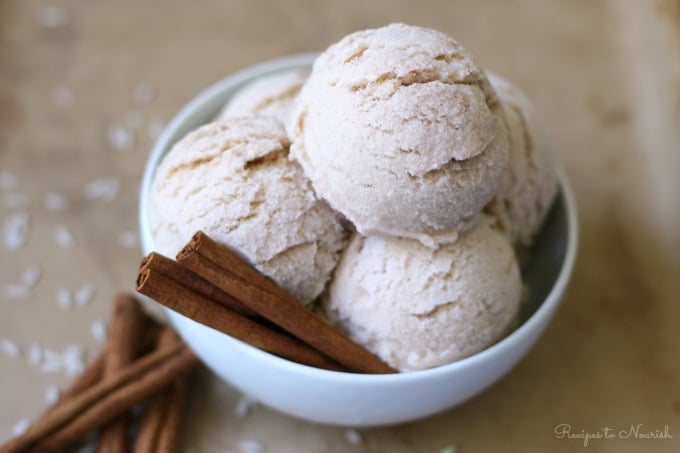 Large bowl with several scoops of ice cream with cinnamon sticks and white rice around it.
