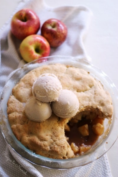 Apple cobbler topped with scoops of ice cream.