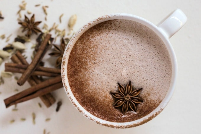 Hot chocolate with ground cinnamon and a star anise pod on top next to chai spices.