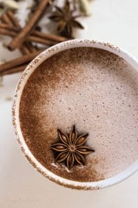 Hot chocolate with ground cinnamon and a star anise pod on top surrounded by chai spices.