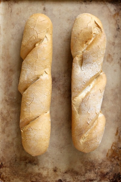 Two baked Udi's baguettes on a baking sheet.