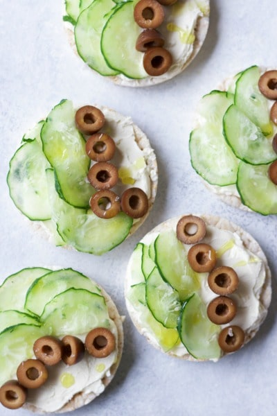 Rice cakes topped with cream cheese, sliced cucumbers and sliced black olives.