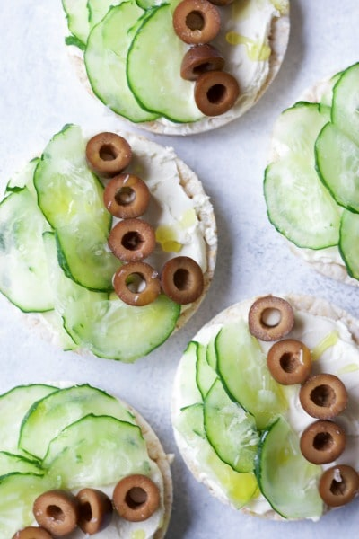 Rice cakes topped with cream cheese, sliced cumbers and sliced black olives.