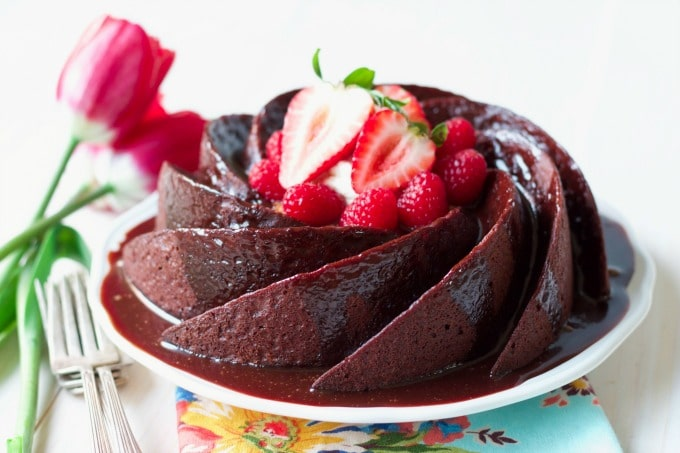 Chocolate cake in a spiral bundt shape, topped with chocolate glaze and fresh berries.