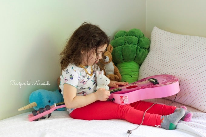 Little girl playing on her bed with her stuffed animals and pink guitar.