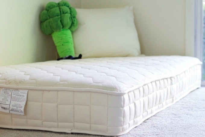Bare organic mattress in a bedroom with a pillow and broccoli stuffed animal.
