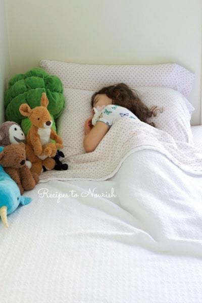 Little girl sleeping in her bed with stuffed animals.