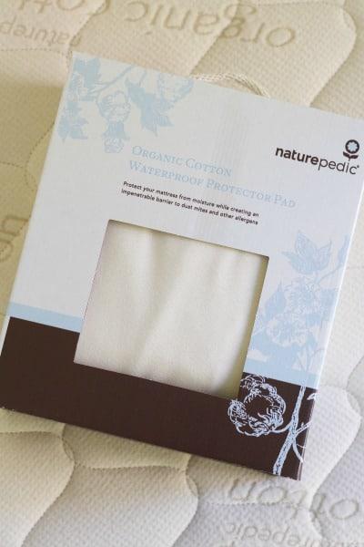 Organic mattress with a box and organic waterproof mattress protector pad inside it.