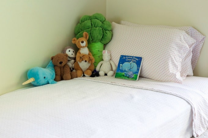 Children's bed with stuffed animals and a bedtime book.