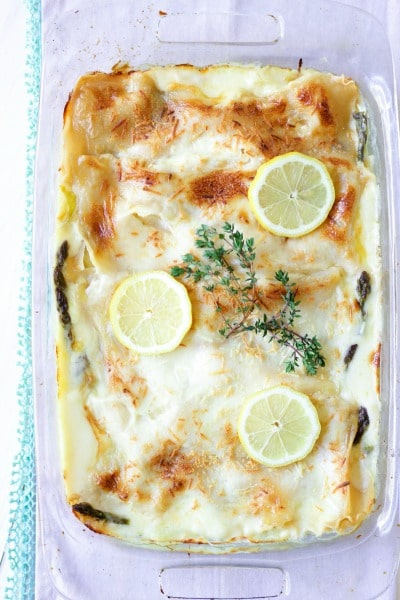 Creamy white sauce lasagna with cheesy top, fresh lemon slices, and fresh thyme.