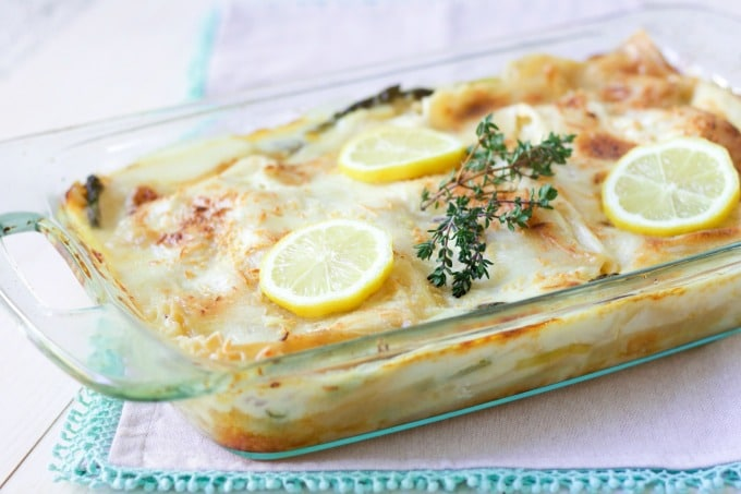 Creamy white sauce lasagna in a casserole dish with cheesy topping, lemon slices and fresh thyme.