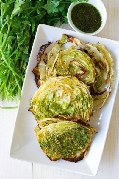 Roasted cabbage steaks with fresh cilantro and chimichurri on the side.
