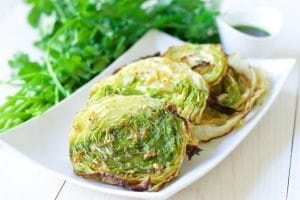 This one sheet pan Garlic Rosemary Roasted Cabbage Steaks side dish is so easy to make and bursting with flavor! It's easy on the budget and deeply flavored with herby aromatics and topped with a vibrant chimichurri sauce. | Recipes to Nourish