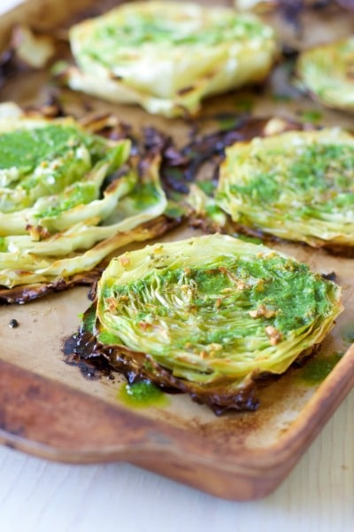 Roasted cabbage steaks on a baking sheet with chimichurri drizzled over the tops.