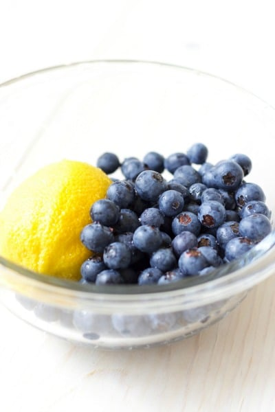 Fresh whole lemon and blueberries in a bowl.