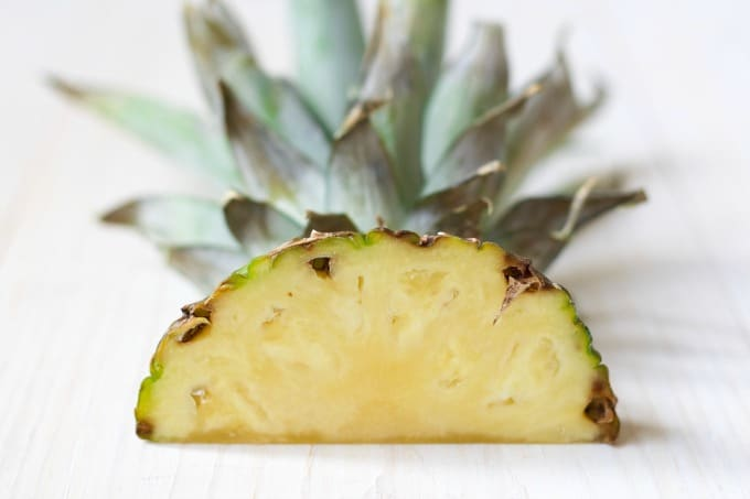 Fresh pineapple top cut in half lying flat.