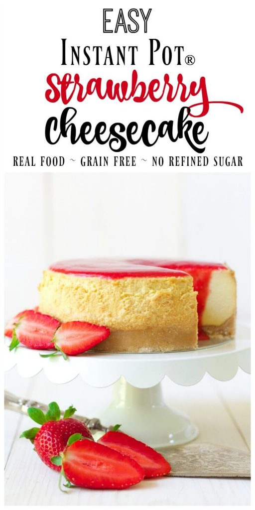 Cheesecake on a cake stand with strawberry sauce on the top and fresh strawberries.