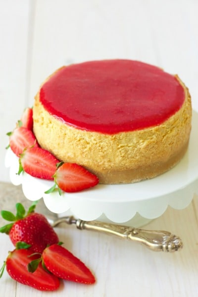 Whole cheesecake with strawberry sauce on the top and fresh strawberries around it.