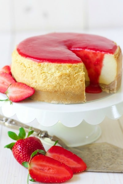 Cheesecake with a slice cut out and strawberry sauce on the top with fresh strawberries.
