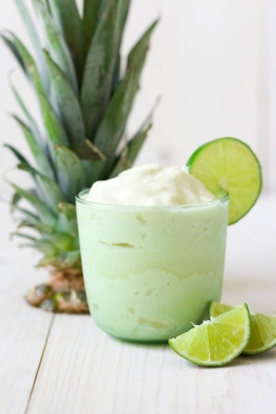 Glass of pineapple whip in a glass with fresh lime slices and pineapple top.