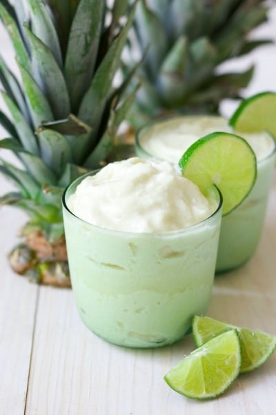 Two glasses of frozen pineapple whip with fresh lime slices and pineapple tops.