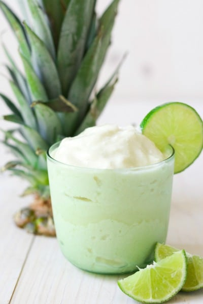 Glass of frozen pineapple whip with fresh lime slices and pineapple top.