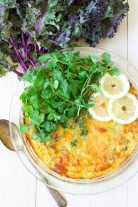 Breakfast casserole with fresh herbs and lemon slices.