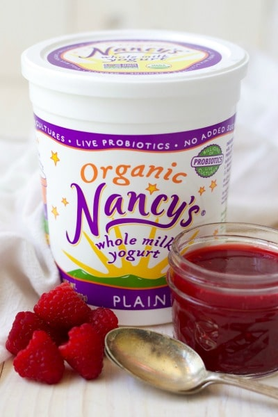 Nancy's organic yogurt with fresh raspberries and raspberry sauce in a jar.
