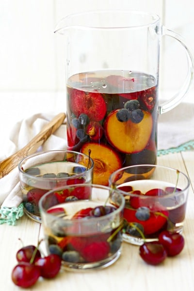 Pitcher and glasses with herbal tea sangria filled with stone fruit and berries.