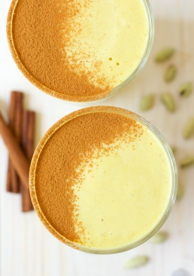 Glasses of golden milk smoothies with ground cinnamon dusted on the top, cinnamon sticks and cardamom pods.