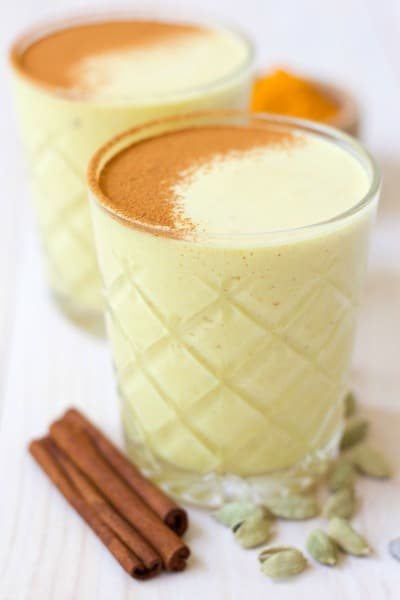 Glasses of golden milk smoothies with cinnamon dusted on the top, cinnamon sticks, cardamon pos and ground turmeric.