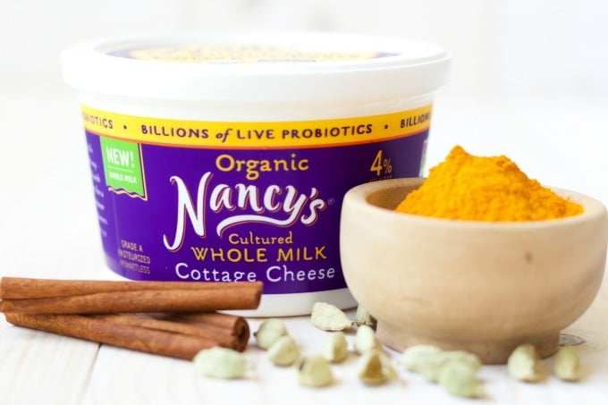 Container of Nancy's organic whole milk cottage cheese, bowl of ground turmeric, cinnamon sticks and cardamom pods.