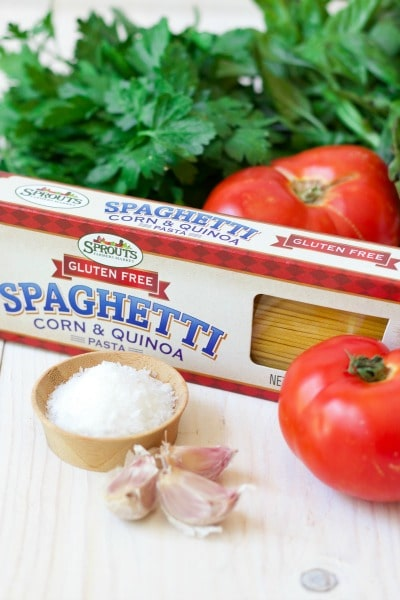 Box of Sprouts Farmers Market gluten-free spaghetti, fresh tomatoes, fresh herbs, garlic and a bowl of salt.