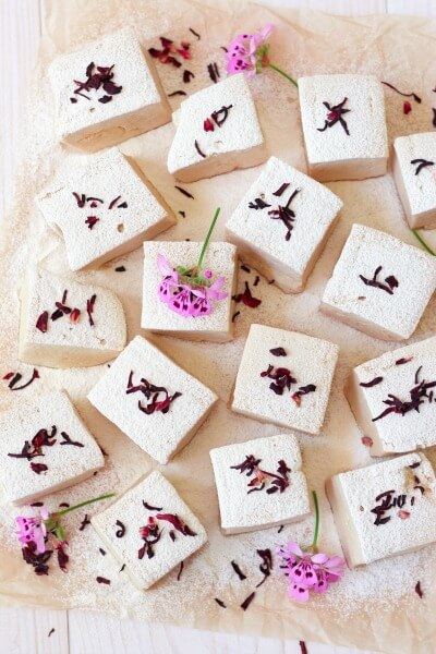 Lots of square cut homemade marshmallows with hibiscus blossoms.