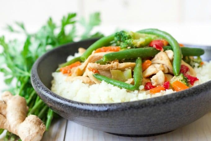 (ad) Thinly sliced chicken stir-fried with frozen vegetables and topped on riced cauliflower is so easy to make! This budget-friendly, Frozen Vegetable Asian Chicken Stir Fry Cauliflower Bowl is packed with a sweet gingery flavor and whips up in 15 minutes, making it a perfect weeknight meal. | Recipes to Nourish