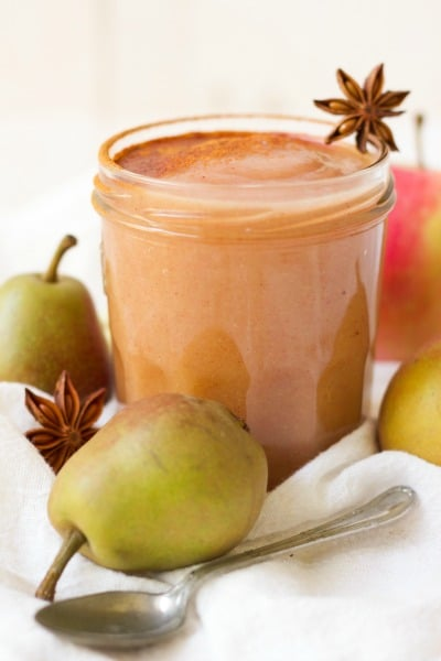 Jar of homemade applesauce dusted with cinnamon surrounded by whole pears and star anise pods.