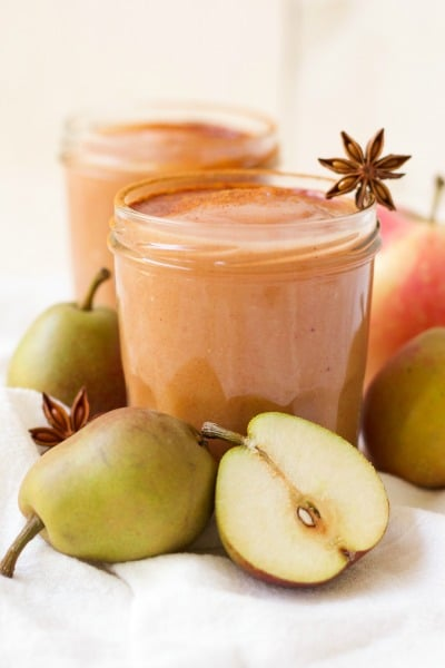Jars of homemade applesauce surrounded by pears and star anise pods.