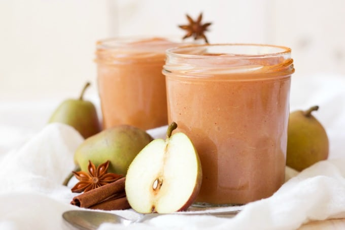 Jars of homemade applesauce surrounded by pears, cinnamon sticks and star anise pods.