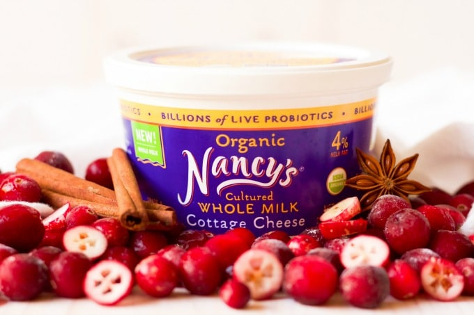 Nancy's organic whole milk cottage cheese container surrounded by cranberries and cinnamon sticks.