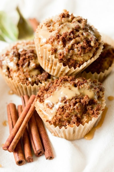 Stacked streusel coffee cake muffins with a maple icing and cinnamon sticks on the side.