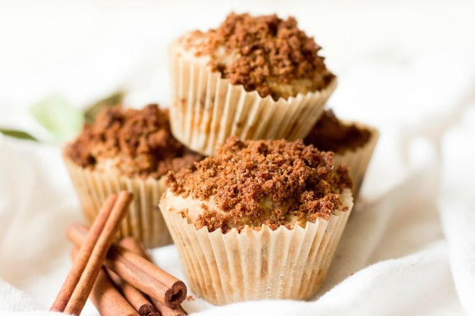 Stacked streusel coffee cake muffins with cinnamon sticks on the side.