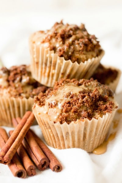 Stacked streusel coffee cake muffins with maple glaze and cinnamon sticks on the side.