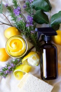 Lemon peels in a mason jar, fresh lemons, fresh rosemary and leaves, kitchen dish sponges and an amber glass spray bottle.