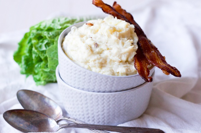 Mashed potatoes in two stacked bowls with crispy bacon and green cabbage.